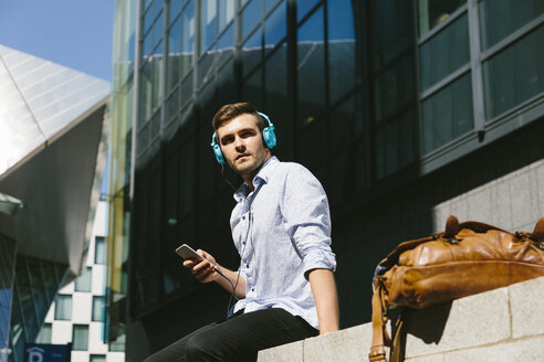 Ireland, Dublin, young businessman sitting on a wall listening music with headphones - BOYF000513
