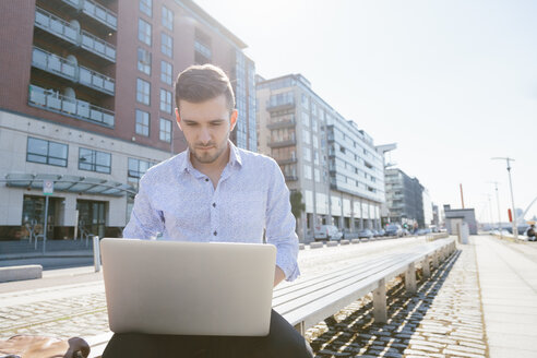Young businessman sitting on bench using laptop - BOYF000525
