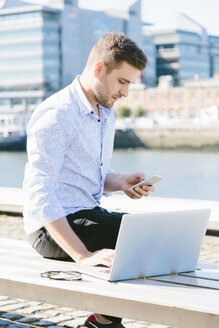 Ireland, Dublin, young businessman sitting on bench using laptop and  cell phone - BOYF000528