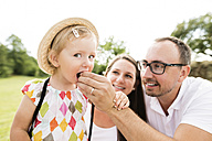 Happy family in park, father feeding daughter - HAPF000732
