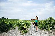 Woman doing tai chi in a vineyard - KIJF000726