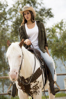 Young woman riding horse at riding stable - ZOCF000131