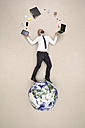 Businessman standing on globe juggling with office devices - BAEF001090