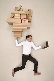 Businessman balancing cardboard boxes and working on laptop - BAEF001156