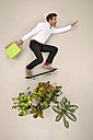 Skateboarding bussinessman in nature with shopping bags - BAEF001189