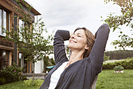 Smiling woman relaxing in garden - RBF004839