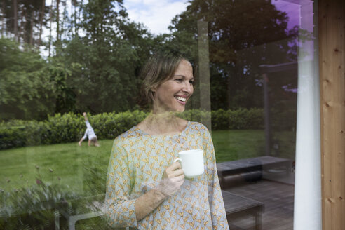 Smiling woman holding cup looking out of window - RBF004845