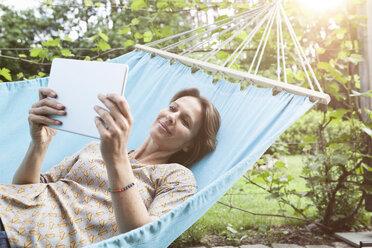 Smiling woman using digital tablet in hammock - RBF004848
