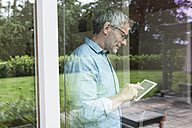 Mature man using digital tablet behind windowpane - RBF004851