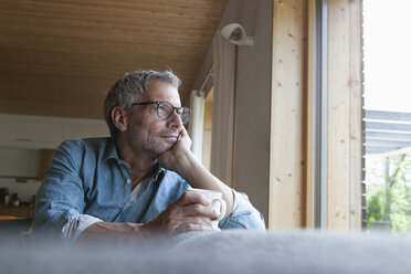 Mature man holding cup sitting on couch - RBF004857