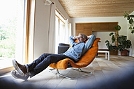 Confident mature man relaxing in armchair - RBF004860