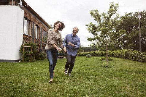 Happy mature couple running in garden - RBF004878