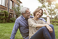 Happy mature couple sitting in garden - RBF004881