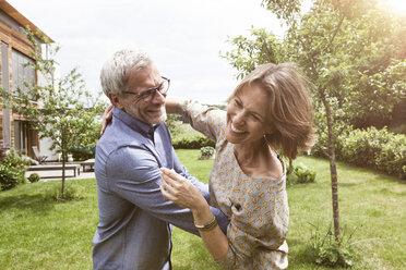 Happy mature couple dancing in garden - RBF004887