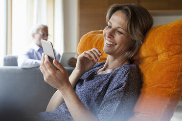 Smiling woman at home looking at cell phone with husband in background - RBF004902