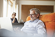 Smiling man using laptop in armchair with wife in background - RBF004905