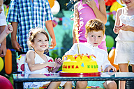 Little girl and little boy celebrating birthday in the garden with friends and family - HAPF000741