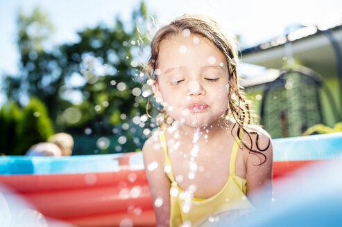 Little girl sitting in paddling pool splashing with water - HAPF000759