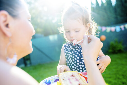 Mother feeding her little daughter with cake in the garden - HAPF000774