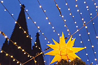 Germany, Cologne, lighted Christmas star with silhouette of spire of Cologne Cathedral in the background - GW004867