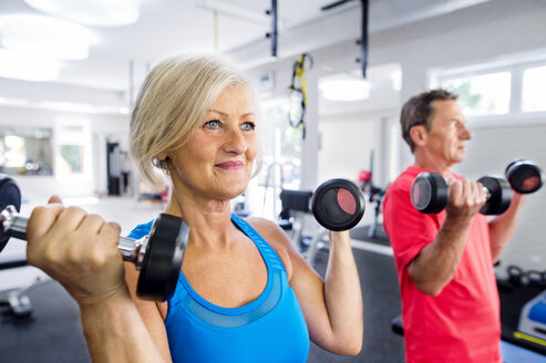 Mature woman and senior man working out in fitness gym - HAPF000777