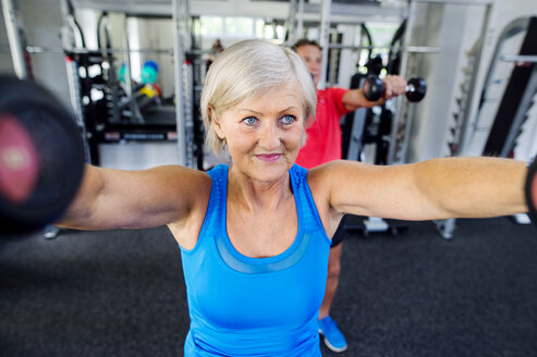 Mature woman and senior man working out in fitness gym - HAPF000783