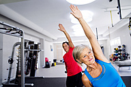 Mature woman and senior man doing gymnastics in fitness gym - HAPF000786