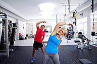 Mature woman and senior man doing gymnastics in fitness gym - HAPF000789