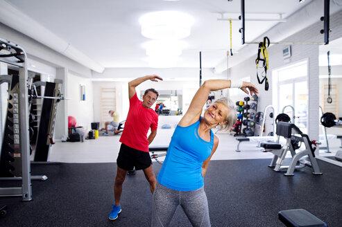 Mature woman and senior man doing gymnastics in fitness gym - HAPF000789