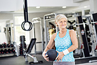 Mature woman holding ball in fitness gym - HAPF000807