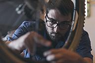 Mechanic in repair shop repairing bicycle - SKCF000167