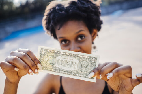 Woman showing one dollar banknote, close-up - GIO001425