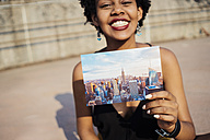 Happy woman showing postcard of New York City - GIOF001428