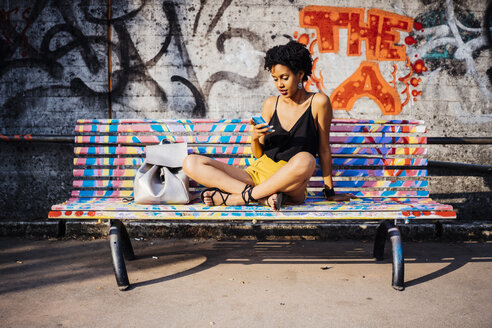 Young woman sitting on colourful painted bench looking at cell phone - GIOF001431