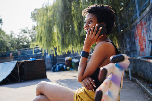 Happy young woman sitting on bench in a skatepark telephoning with cell phone - GIOF001434