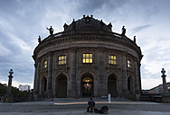 Germany, Berlin, view to lighted Bode Museum at Museumsinsel with street musician in the foreground - FC001031