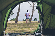 Back view of young woman standing on a meadow in front of a tent - DAPF000257