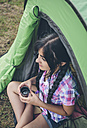 Young woman sitting in front of a tent with cup of coffee - DAPF000263
