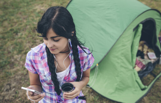 Young woman in front of a tent with cup of coffee listening music with earphones - DAPF000266