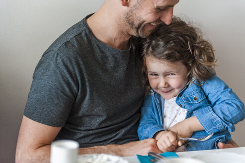 Father and daughter having fun at breakfast table - DIGF000963