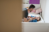 Father tickling daughter in bed - DIGF000975