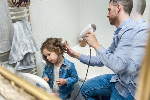 Father blow-drying daughter's hair - DIGF001002