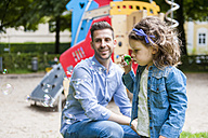 Daughter with father on playground blowing soap bubbles - DIGF001020