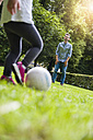 Father and daughter playing football in park - DIGF001023