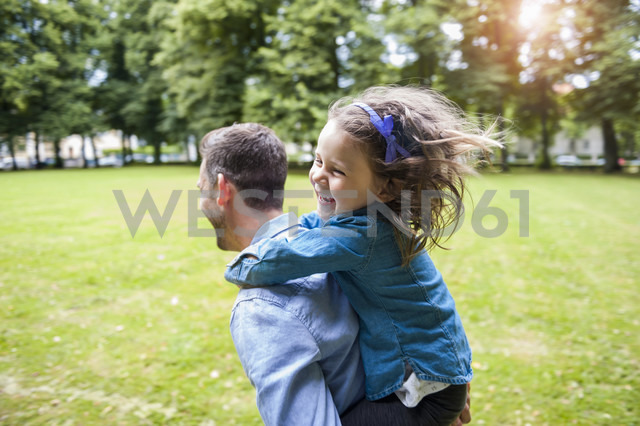 Father carrying daughter on shoulders in park - DIGF001032