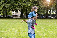 Father carrying daughter on shoulders in park - DIGF001035