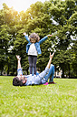 Father and daughter playing on meadow in park - DIGF001041