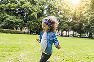 Happy girl running on meadow in park - DIGF001044