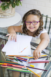 Portrait of smiling girl painting with coloured pencils - ABZF000973