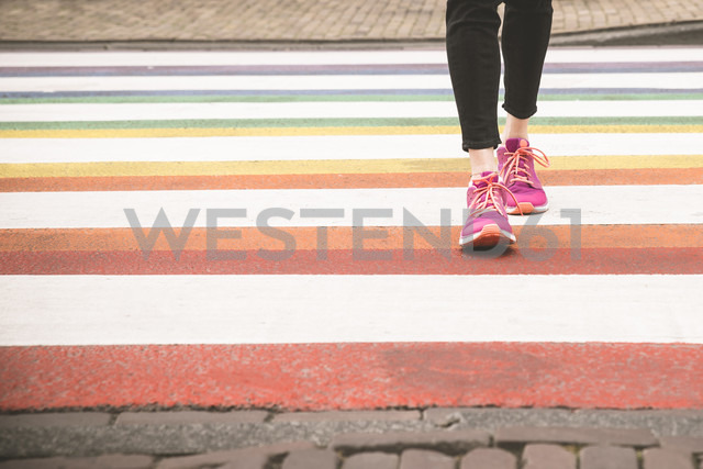 Woman crossing multi coloured zebra crossing, partial view - CHPF000287